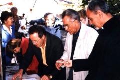 François Corbineau présente le protocole d'accord de jumelage au Père Yacoub S'ada qui passe son stylo au Père André Neau